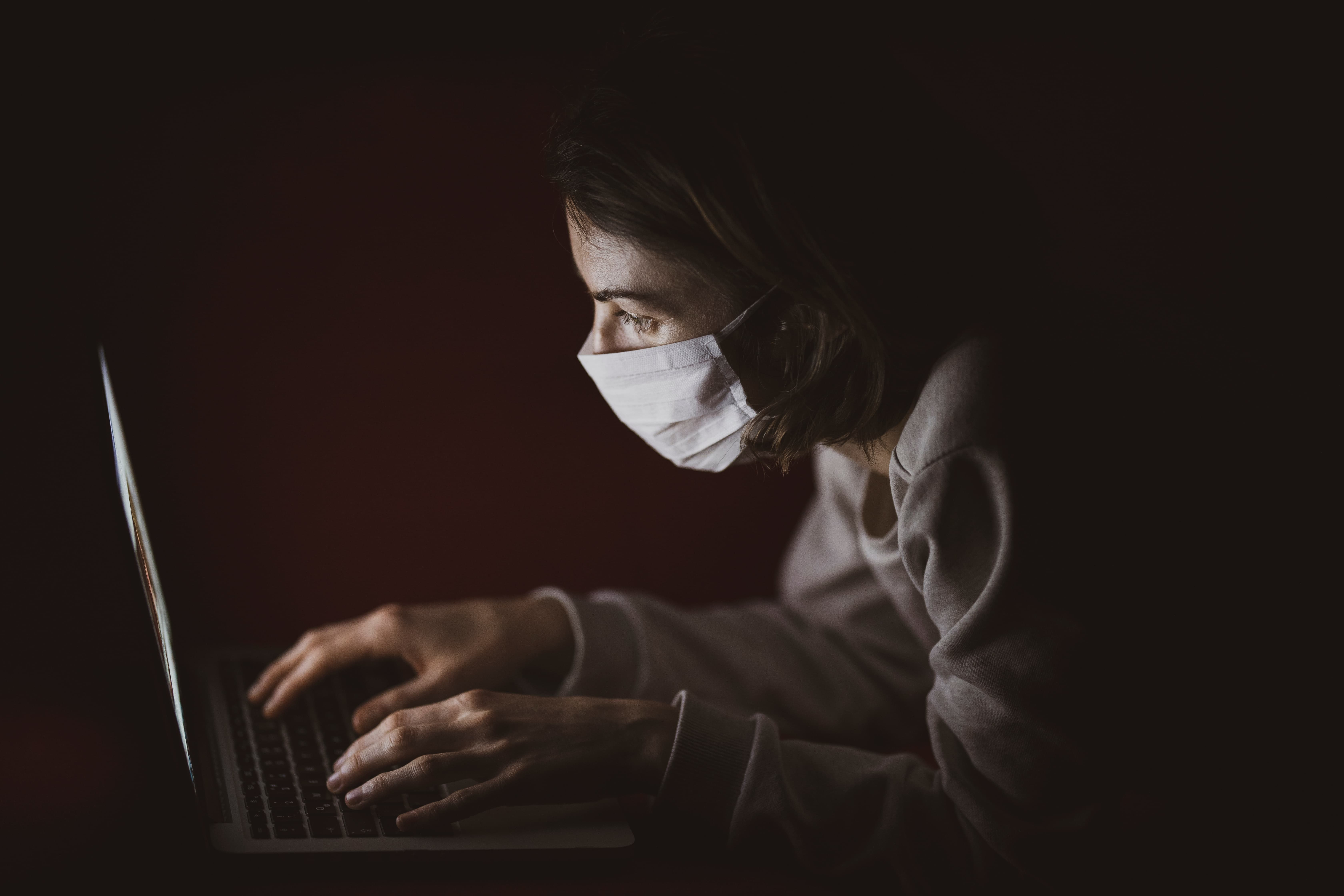 lady in front of laptop wearing mask in a dark room