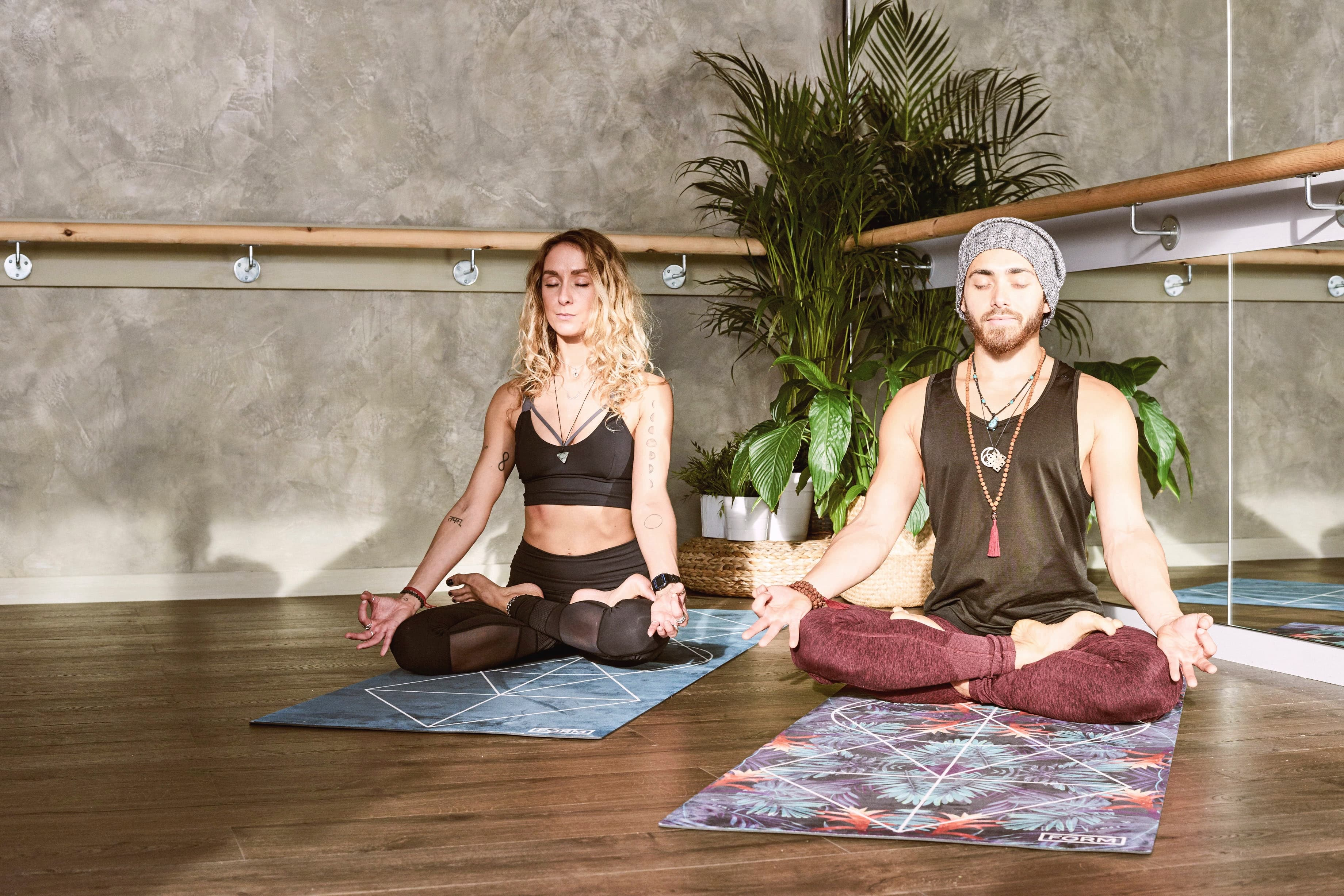 man and woman meditating indoors
