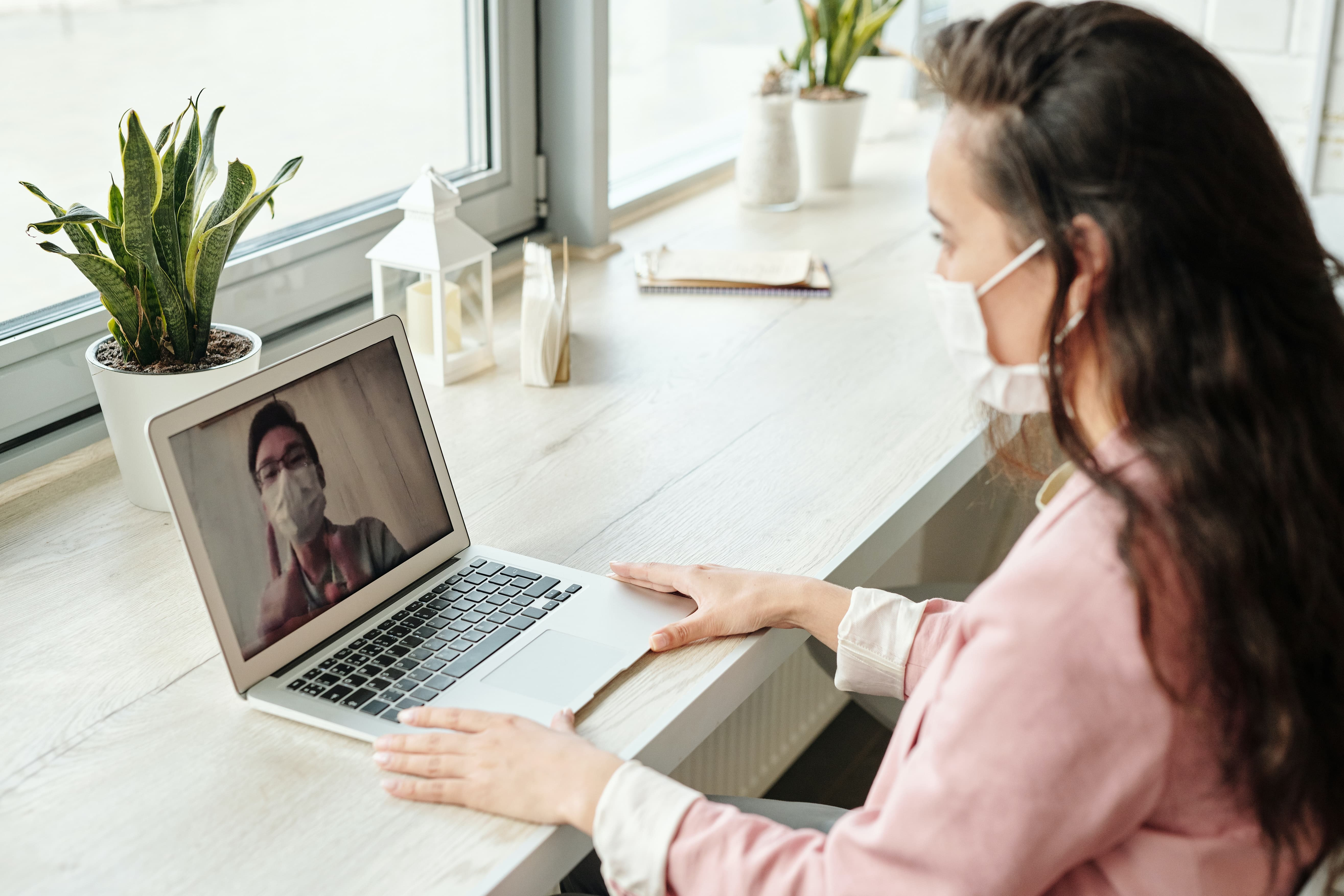 women wearing mask having a video call